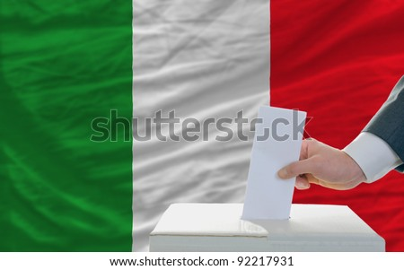 man putting ballot in a box during elections in italy in front of flag - stock photo
