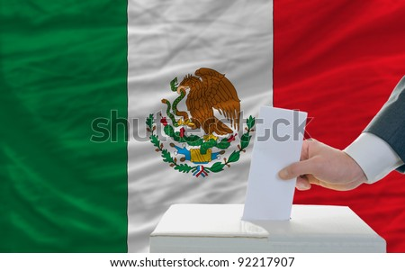 man putting ballot in a box during elections in mexico in front of flag - stock photo