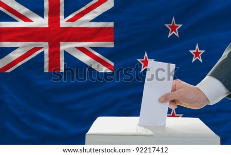 man putting ballot in a box during elections in new zealand in front of flag - stock photo