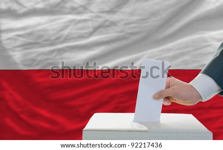 man putting ballot in a box during elections in poland in front of flag - stock photo