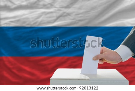 man putting ballot in a box during elections in russia - stock photo