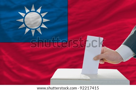 man putting ballot in a box during elections in sri lanka in front of flag - stock photo