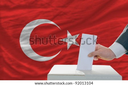 man putting ballot in a box during elections in turkey - stock photo