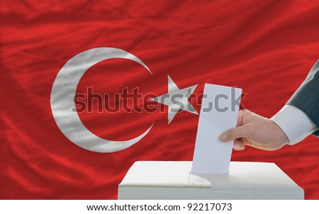 man putting ballot in a box during elections in turkey in front of flag - stock photo