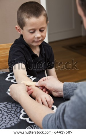 Man putting Band-Aid on sons arm - stock photo