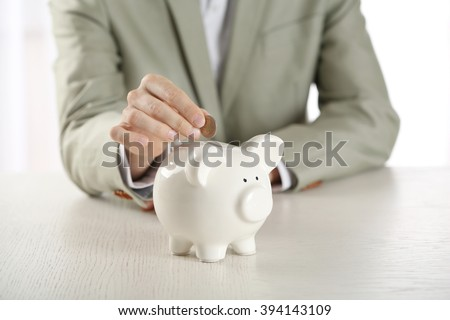 Man putting coin into piggy bank at wooden table closeup