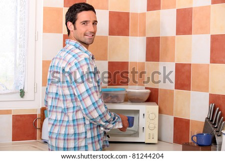 Man putting cup in microwave - stock photo