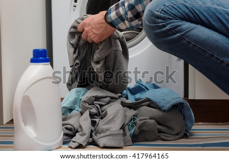 Man putting dirty clothes into opened washing machine - stock photo