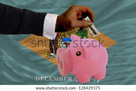 Man putting dollar into piggy rich bank flag of us state of delaware in foreign currency because of inflation - stock photo
