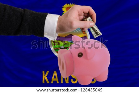Man putting dollar into piggy rich bank flag of us state of kansas in foreign currency because of inflation - stock photo