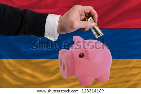 Man putting dollar into piggy rich bank national flag of armenia in foreign currency because of inflation - stock photo