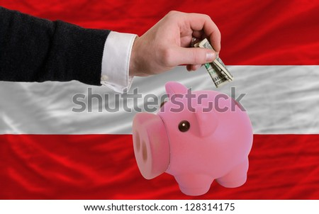 Man putting dollar into piggy rich bank national flag of austria in foreign currency because of inflation - stock photo