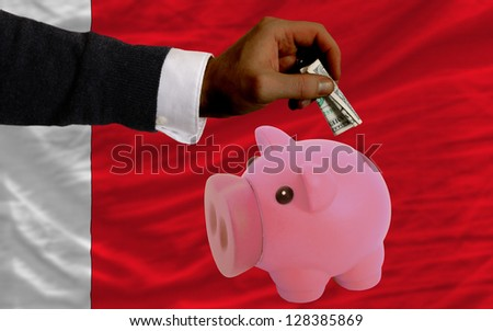 Man putting dollar into piggy rich bank national flag of bahrain in foreign currency because of inflation - stock photo