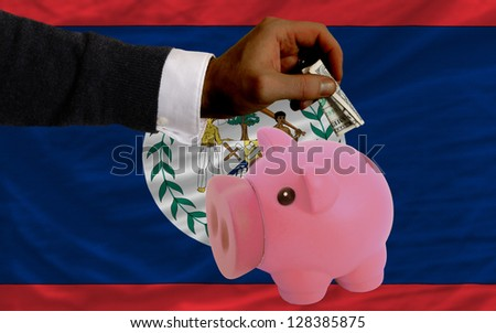 Man putting dollar into piggy rich bank national flag of belize in foreign currency because of inflation - stock photo