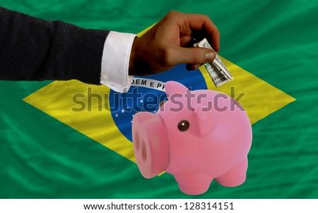 Man putting dollar into piggy rich bank national flag of brazil in foreign currency because of inflation - stock photo
