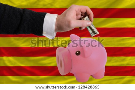 Man putting dollar into piggy rich bank national flag of  catalonia in foreign currency because of inflation - stock photo