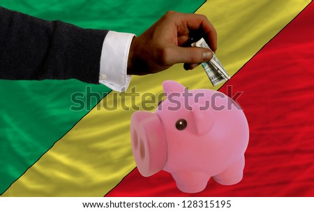 Man putting dollar into piggy rich bank national flag of  congo in foreign currency because of inflation - stock photo