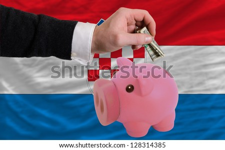 Man putting dollar into piggy rich bank national flag of croatia in foreign currency because of inflation