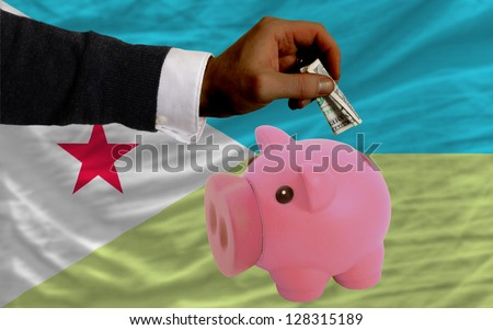 Man putting dollar into piggy rich bank national flag of  djibuti in foreign currency because of inflation - stock photo