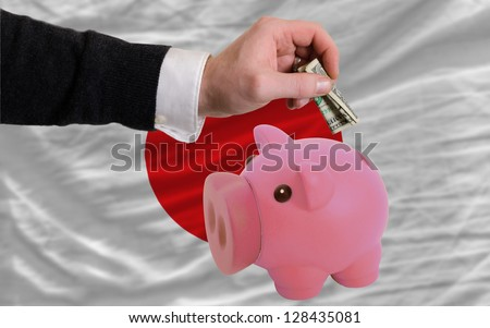 Man putting dollar into piggy rich bank national flag of japan in foreign currency because of inflation - stock photo