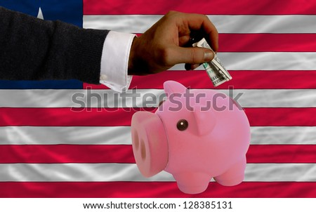 Man putting dollar into piggy rich bank national flag of liberia in foreign currency because of inflation - stock photo