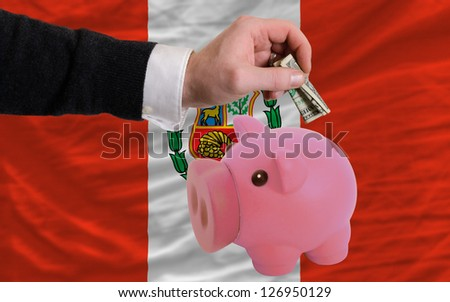 Man putting dollar into piggy rich bank national flag of peru in foreign currency because of inflation - stock photo