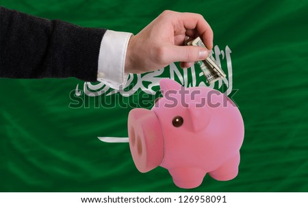 Man putting dollar into piggy rich bank national flag of  saudi arabia in foreign currency because of inflation - stock photo