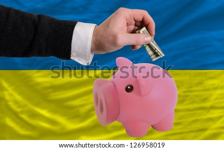 Man putting dollar into piggy rich bank national flag of ukraine in foreign currency because of inflation - stock photo