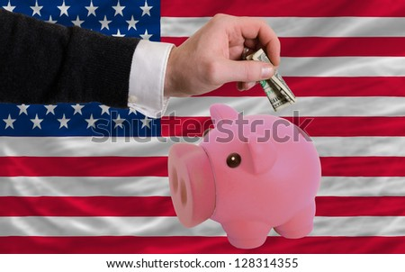 Man putting dollar into piggy rich bank national flag of us in foreign currency because of inflation - stock photo