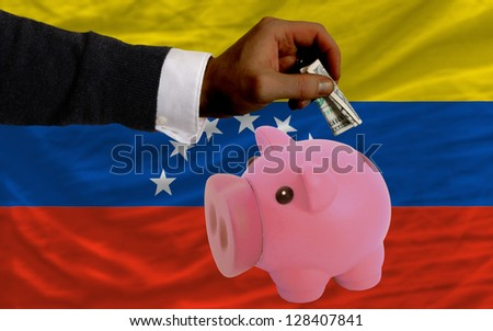 Man putting dollar into piggy rich bank national flag of venezuela in foreign currency because of inflation - stock photo