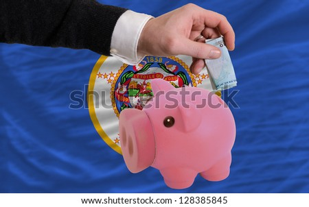 Man putting euro into piggy rich bank and flag of us state of minnesota in foreign currency because of insecurity and inflation