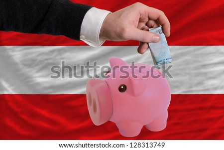 Man putting euro into piggy rich bank and national flag of austria in foreign currency because of insecurity and inflation - stock photo