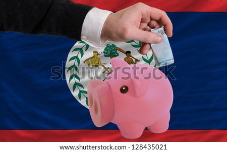 Man putting euro into piggy rich bank and national flag of belize in foreign currency because of insecurity and inflation - stock photo