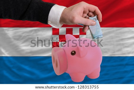Man putting euro into piggy rich bank and national flag of croatia in foreign currency because of insecurity and inflation - stock photo