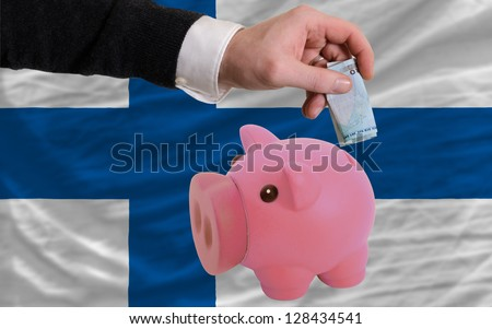 Man putting euro into piggy rich bank and national flag of finland in foreign currency because of insecurity and inflation - stock photo