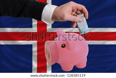 Man putting euro into piggy rich bank and national flag of iceland in foreign currency because of insecurity and inflation - stock photo