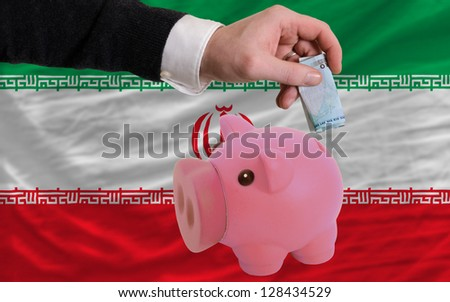 Man putting euro into piggy rich bank and national flag of iran in foreign currency because of insecurity and inflation - stock photo