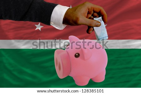 Man putting euro into piggy rich bank and national flag of  maghreb in foreign currency because of insecurity and inflation - stock photo