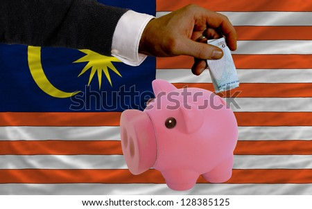 Man putting euro into piggy rich bank and national flag of malaysia in foreign currency because of insecurity and inflation