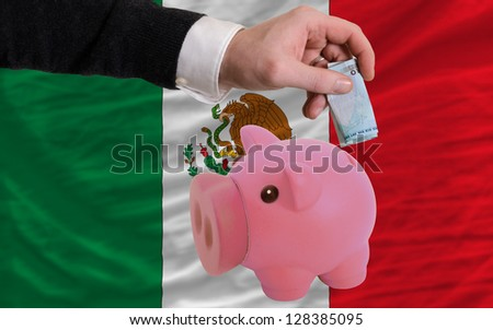 Man putting euro into piggy rich bank and national flag of mexico in foreign currency because of insecurity and inflation - stock photo