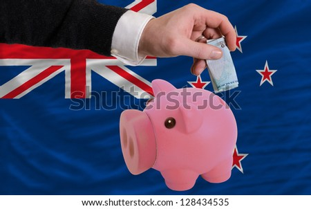 Man putting euro into piggy rich bank and national flag of new zealand in foreign currency because of insecurity and inflation - stock photo