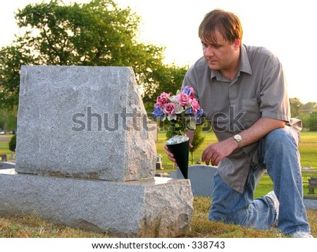 Man putting flowers on grave - stock photo