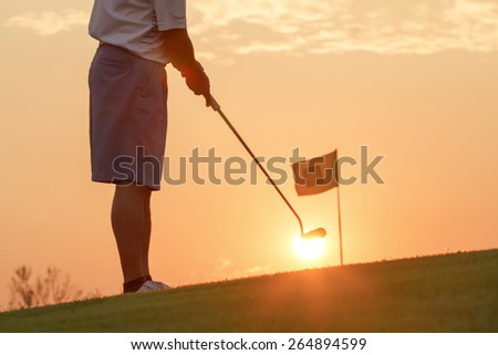 Man putting golf ball against sunset - stock photo