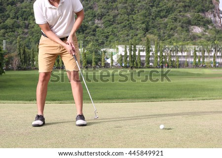 Man putting golf ball with hole