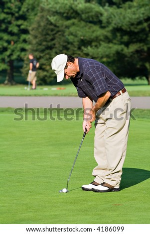 Man putting in a golf shot on a summer day. - stock photo