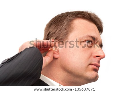 Man putting on a hearing aid isolated on white