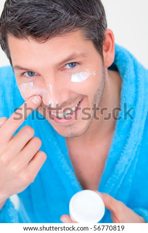 Man putting on cream lotion on face - stock photo