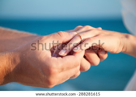 Man putting on golden ring on a woman's finger, sea background - stock photo