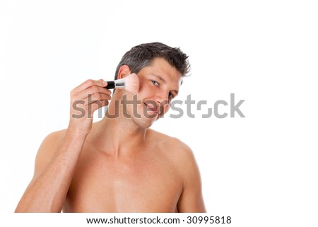 Man putting on make up and powdering his face - stock photo