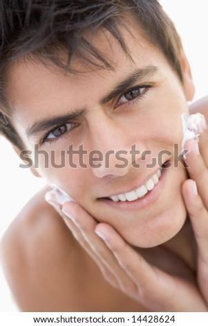 Man putting on shaving cream smiling - stock photo